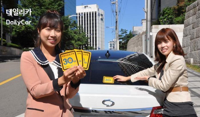 1004 르노삼성과 행정안전부가 전개하는 스쿨존캠페인스티커를 차에 부착하는모습