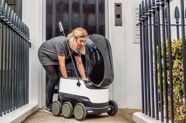 한 여성이 배송로봇에서 물건을 꺼내고 있다, 출처: 에스토니안 월드