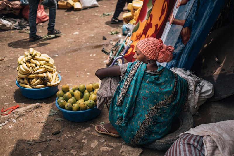 화려한 패턴이 매력적인 전통 옷을 입고 과일을 판매하는 여인